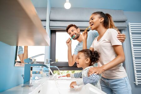 Mother, father and daughter brushing teeth in bathroom