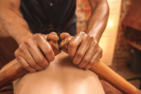 Alternative medicine and spa salon woman lying on medical bed while therapist doing back and shoulder massage using hollow bamboo canes with oil close-up