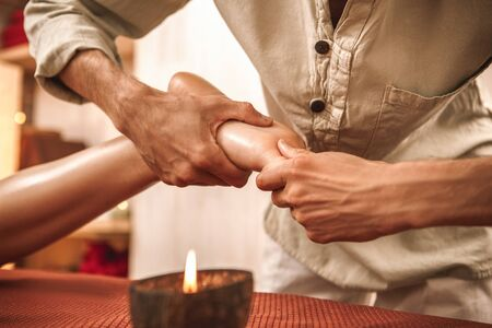 Alternative medicine salon therapist healing woman doing ayurvedic massage acupressure rubbing foot concentrated close-up with aroma candle