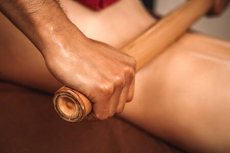 Alternative medicine and spa salon woman lying on medical bed while therapist doing massage using hollow bamboo cane rolling on back oily hands close-up