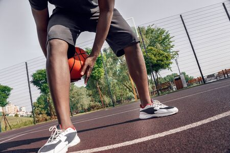 Young african man playing on court outdoors dribbling basketball between legs technique close-up