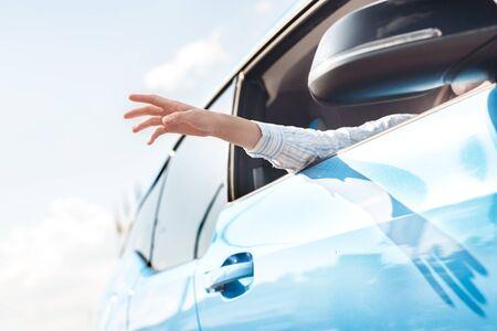 Junge Frau, die mit dem neuen Elektroauto-Transport mit der Hand aus dem Fenster reist und die Winduntersicht Nahaufnahme fängt