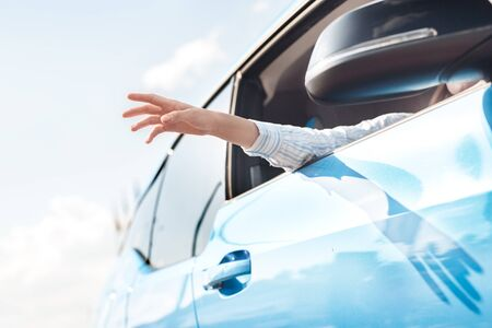 Young woman traveling by new electric car transportation hand out of the window catching wind bottom view close-up