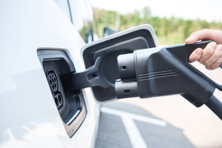 Young woman traveling by electric car having stop at charging station standing plugging charging cable side view close-up