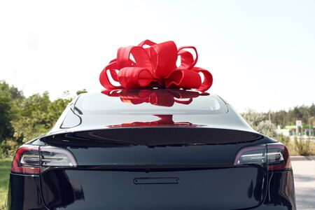 Electric black car with ribbon bow luxury present outdoors back view close-up Banque d'images - 137835771