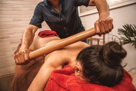 Alternative medicine and spa salon woman lying on medical bed naked while therapist doing massage using hollow bamboo cane rolling on back close-up