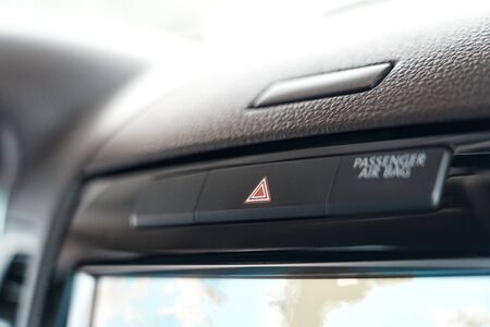 Selective focus of red warning triangle sign in modern automobile and emergency button in car. Element of interior inside transport with copy space on background Banque d'images