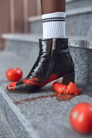 Young stylish woman wearing hills and socks walking down the stairs outdoors urban background stepping on tomatoes foot close-up 版權商用圖片