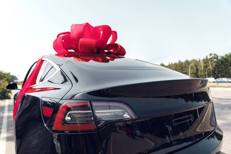 Electric black car with ribbon bow luxury present outdoors side view close-up