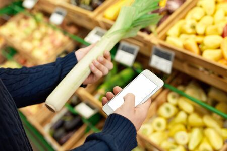 Young man at the supermarket doing daily shoppings holding celery browsing internet on smartphone checking price blurred background just walk out shopping technology