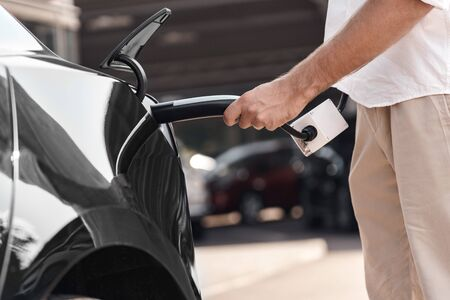 Cropped view of man standing near electric car, charging automobile battery from small public station and holding conector plugging in hands Zdjęcie Seryjne