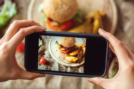 Young man sitting at table at restaurant having lunch taking photos of hamburger and french fries on smartphone close-up blurred background