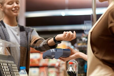 Young adult woman paying for shopping using smart watch and terminal