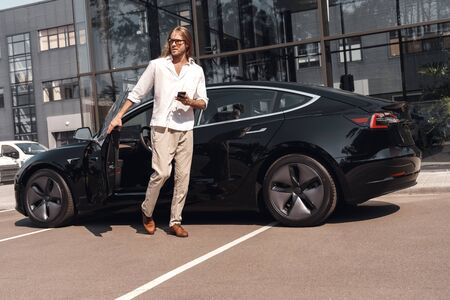 Mode of Transport. Man with long hair going out of electric car with smartphone looking aside curious