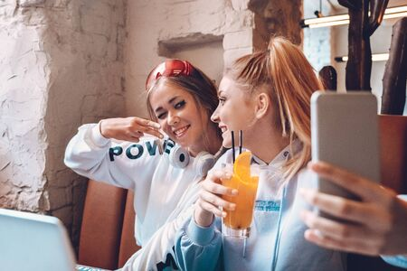 Two teenage girls sitting in cafe, making selfie photo Stock fotó