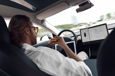Mode of Transport. Bearded man with long hair in sunglasses traveling sitting inside electric car driving on autopilot watching video on digital tablet concentrated