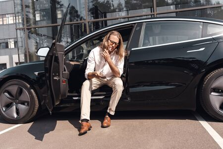 Mode of Transport. Man with long hair in sunglasses sitting at electric car smoking cigarette thoughtful