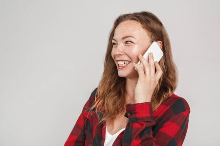 Freestyle. Young woman with freckles standing isolated on grey talking on phone laughing cheerful