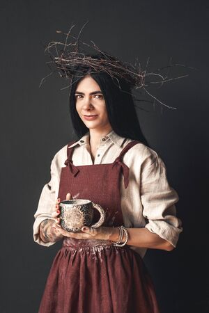 Craftsperson Concept. Young woman artist in twig wreath standing isolated on dark with handmade cup smiling confident