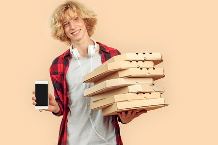 Young adult guy with carton pizza boxes showing smartphone with copy space