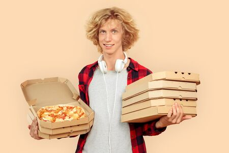 Young adult guy with carton pizza boxes looking at camera