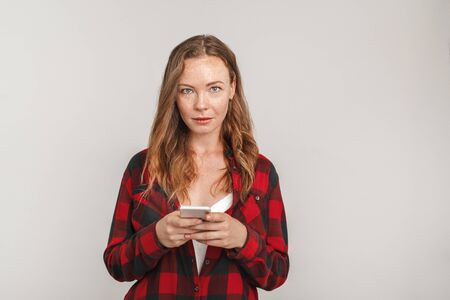 Freestyle. Young woman with freckles standing isolated on grey browsing smartphone smiling curious