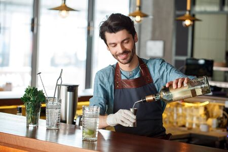 Making Drink. Bartender standing at counter pouring rum into shot cup smiling cheerful