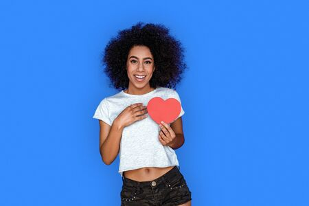 Valentines Day. Mulatto girl standing isolated on blue with valentine touching chest admired Imagens
