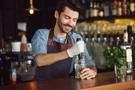 Drink Preparation. Bartender standing at counter squeezing out lime juice smiling concentrated