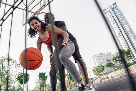 Outdoors Activity. African couple on basketball court girl dribbling while man blocking her from back laughing happy bottom view