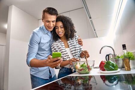 ロマンチックな日付。キッチン料理の夕食に立っている若い多民族カップルは、好奇心旺盛なスマートフォンでレシピビデオを見てサラダを見て妻を抱きしめる夫