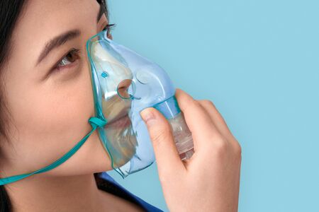 Freestyle. Chinese woman in oxygen mask standing isolated on grey breathig side view clsoe-up
