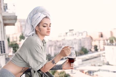 Young adult woman on balcony smoking cigarette, holding wine glass