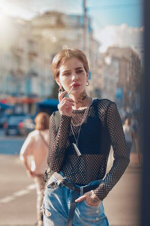 Urban Style. Young stylish woman standing hand in pocket outdoors smoking cigarette looking aside pensive
