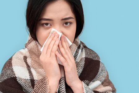 Young adult asian woman with runny nose and napkin in hands