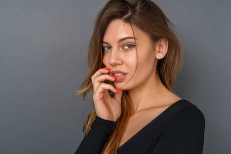 Young woman in a black bodysuit studio isolated on gray touching lips sensual Reklamní fotografie