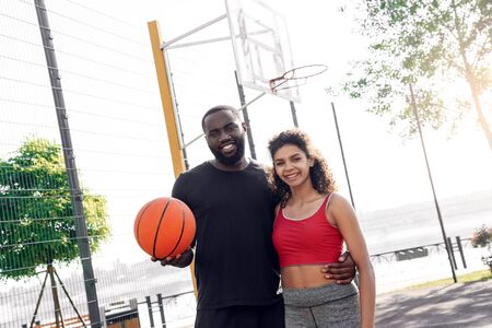 Outdoors Activity. African couple standing on basketball court with ball hugging smiling joyful