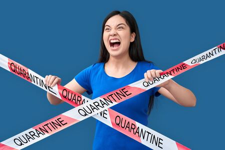 Young adult asian girl screaming, standing behind caution line