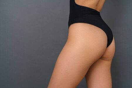 Young woman in a black bodysuit studio isolated on gray hips close-up
