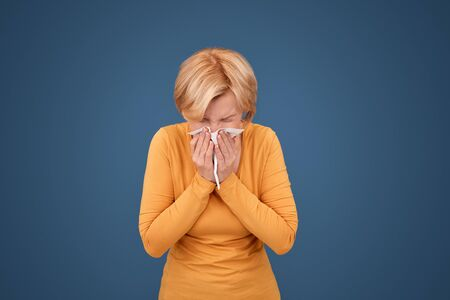Mature woman sneezes into napkin, standing against blue background