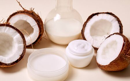 Halved organic coconuts and body cream in jar isolated on background Archivio Fotografico