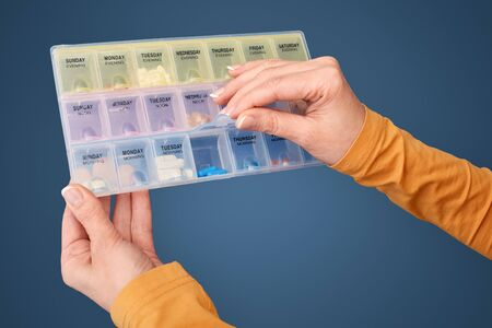 Cropped view of mature woman opened plastic organizer box with pills, standing isolated on blue background