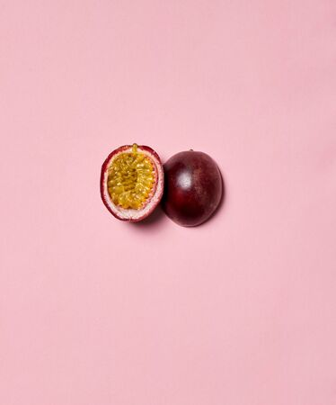 Concept of fresh and juicy fruits. Flat lay of yummy and sliced passion fruit lying on pastel pink background with copy space