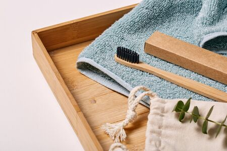 Eco-friendly bamboo toothbrush on wooden tray with towel morning grooming