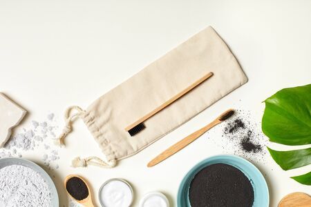 Eco-friendly bamboo toothbrush on textile bag and black charcoal powder paste natural cleanser top view isolated on white background Stock fotó
