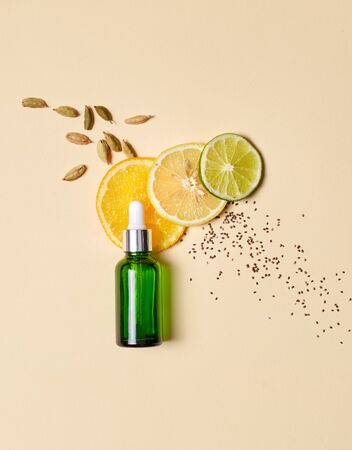 Concept of natural beauty products. Flat lay of serum oil with pipette and citrus vitamin component and fresh ingredients on pastel background