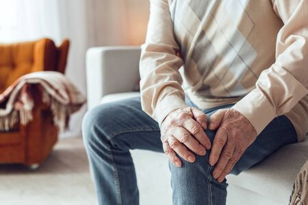 Senior man alone sitting on sofa at library holding knee close-up having pain Imagens
