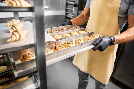 Young man wearing gloves standing at bakery shop small business holding tray of cinnamon rolls baking close-up