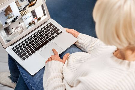 Senior woman wearing sweater at home sitting on sofa at home using laptop doing online shopping screen close-up back view Stock Photo