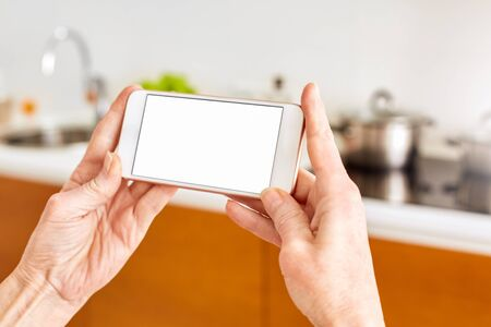 Senior woman at home standing at kitchen holding smartphone controlling smart home system hands close-up mockup copy space for text or product
